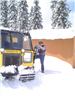 Man scrapes snow off of Snowcat vehicle