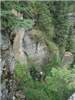 Man rappelling down large cliff
