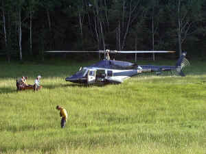 Search and Rescue helicopter and team searching in grassy area